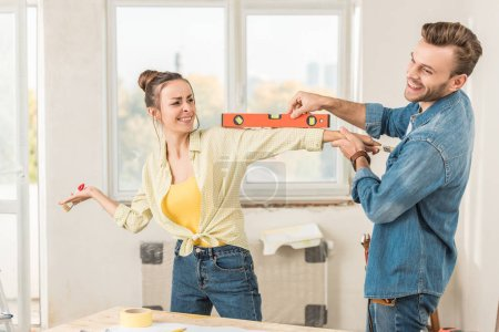 Photo for Happy young couple having fun with tools during repairment - Royalty Free Image