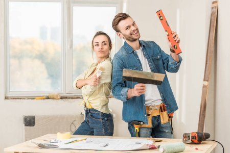 happy young couple holding renovation tools and smiling at camera in new apartment