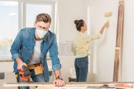 Photo pour Jeune homme en vêtements de travail protecteurs à l'aide de la sauteuse et regardant la caméra tout mur peinture épouse derrière - image libre de droit