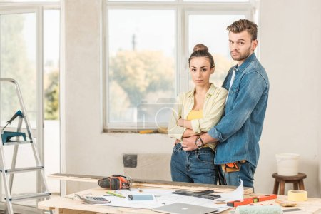 Photo for Serious young couple embracing and looking at camera during house repairment - Royalty Free Image