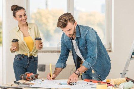 Foto de Sonriente joven mujer sosteniendo las tazas de papel y mirando marido marca modelo y uso de la tableta digital - Imagen libre de derechos
