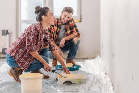 happy young couple in checkered shirts painting wall together in new apartment