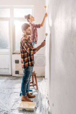 side view of young couple holding paint rollers and painting wall in new apartment