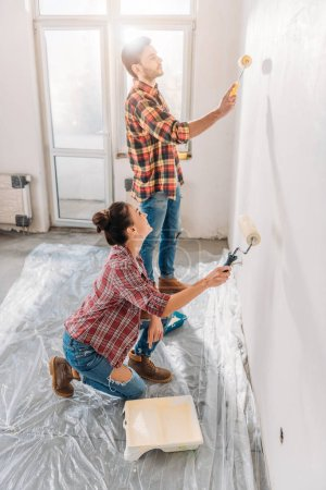 high angle view of young couple holding paint rollers and painting wall in new apartment
