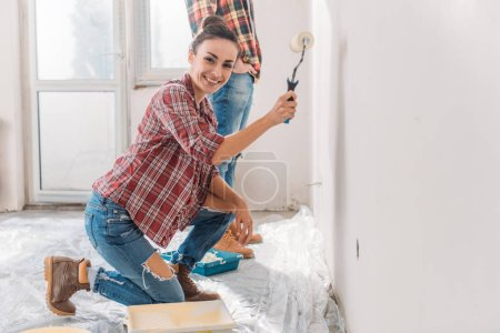 Photo for Happy young woman painting wall and smiling at camera in new apartment - Royalty Free Image