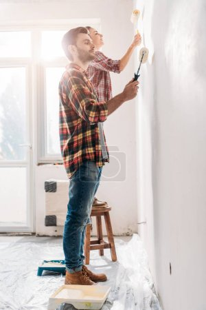 side view of young couple painting wall in new house