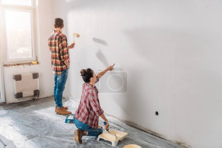 high angle view of young couple painting wall in new house