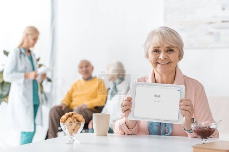 senior woman holding digital tablet with google app in nursing home with people at background