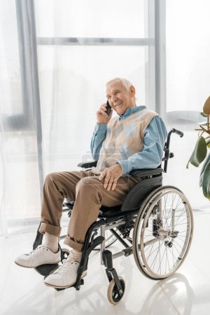 Photo for Senior smiling man sitting in wheelchair and talking on smartphone in nursing home - Royalty Free Image