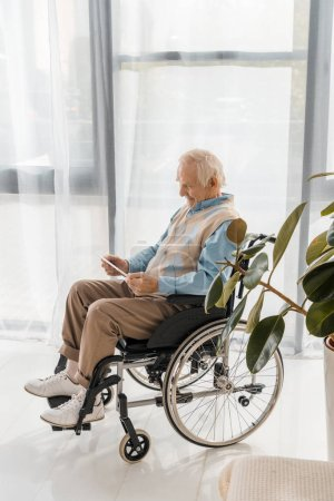 senior smiling man sitting in wheelchair and using digital tablet in nursing home