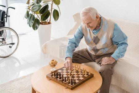 senior man sitting on sofa and playing chess