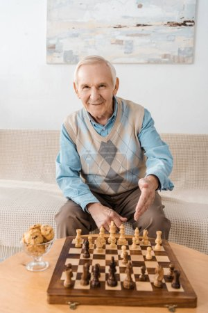 smiling senior man sitting on sofa and playing chess