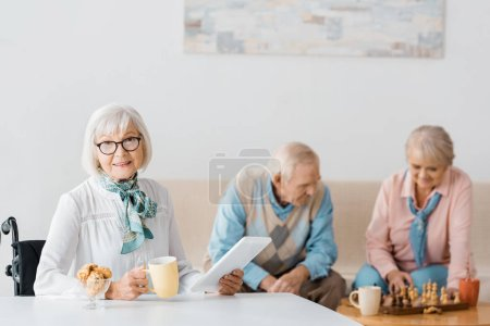 senior woman drinking tea with cookies while senior couple playing chess