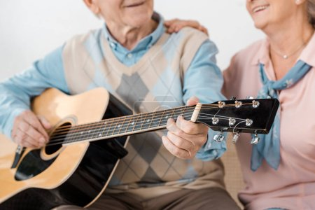 close up of senior man playing acoustic guitar with smiling senior woman