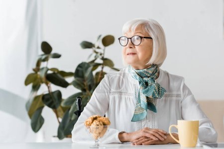 senior woman in glasses sitting at table with cup and cookies