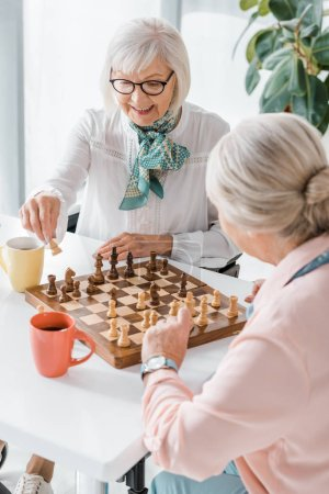 senior women playing chess and drinking coffee in nursing home