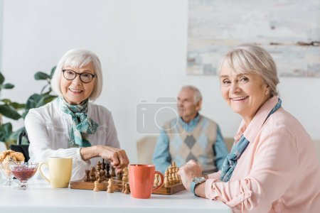 senior women playing chess and drinking coffee while senior man sitting on sofa