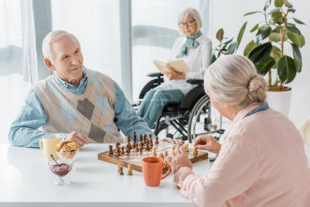 senior couple playing chess while senior woman sitting in wheelchair and reading book