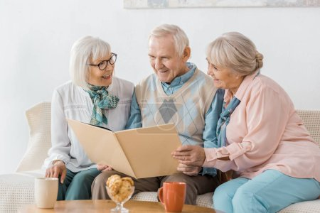 senior smiling people sitting on sofa and reading book together