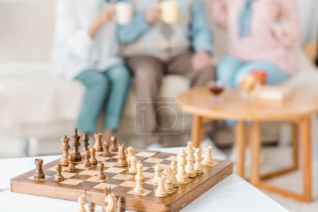 wooden chess desk with figures and blurred people at background