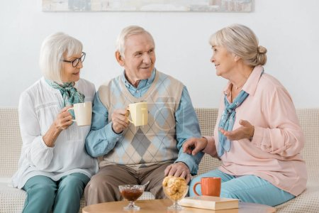 senior people drinking coffee and talking in nursing home