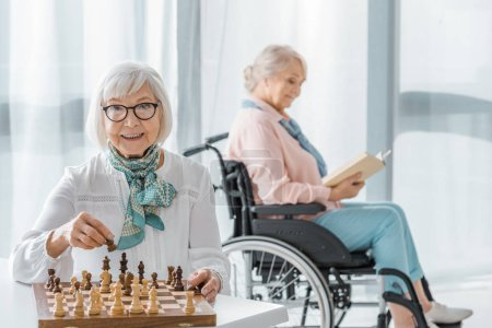 senior woman playing chess at table while another sitting in wheelchair and reading book