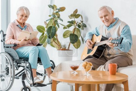senior woman sitting in wheelchair and reading book while senior man playing acoustic guitar