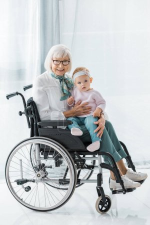 smiling grandmother in wheelchair holding small granddaughter