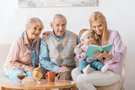 happy family sitting on sofa and reading book with toddler