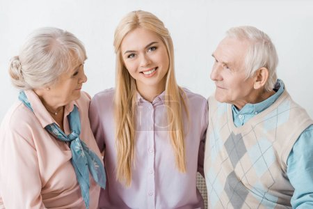 young smiling woman hugging senior parents