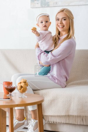 Photo for Young woman sitting on sofa with small daughter holding cookie - Royalty Free Image