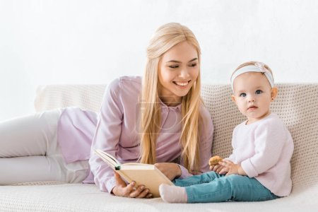 young smiling mother reading book to small daughter while toddler holding cookie