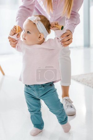 toddler daughter walking with mother while holding chess figure and cookie in hands
