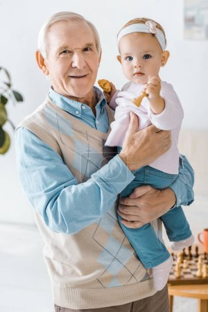 senior grandfather holding toddler granddaughter with cookie and chess figure in hands