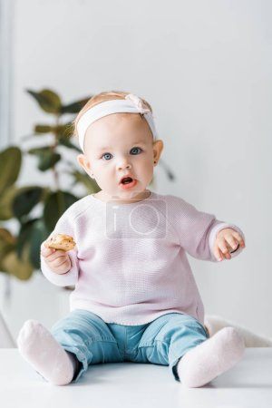 cute toddler sitting on white table and holding biscuit