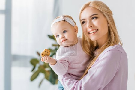 Photo for Young mother holding small cute daughter with cookie - Royalty Free Image