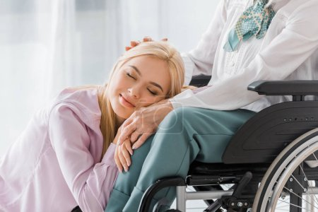 young woman with closed eyes laying on senior woman knees in wheelchair