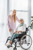 young woman standing near senior woman in wheelchair and looking at camera