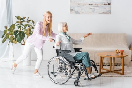 young woman pushing wheelchair with happy senior woman in nursing home