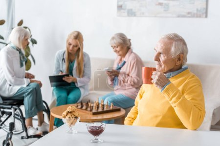senior man drinking tea while doctor examining senior women