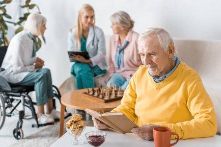 senior man reading book while female doctor examining senior women