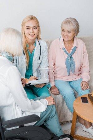young female nurse sitting on sofa and talking to senior women