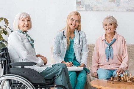 young female nurse sitting on sofa and writing prescription to senior women