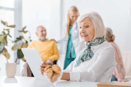 senior woman using digital tablet at nursing home with blurred people at background