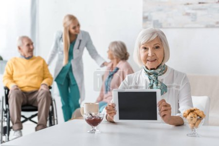senior woman holding digital tablet at nursing home with senior people and doctor at background