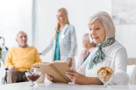 Photo pour Livre de lecture Senior femme au foyer avec des gens flous à fond - image libre de droit