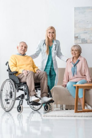 young cheerful female doctor talking to senior people at nursing home
