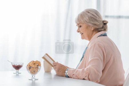 senior woman sitting at table and reading book in nursing home
