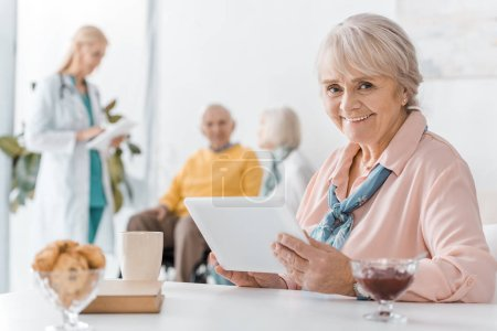 senior woman using digital tablet at table in nursing home