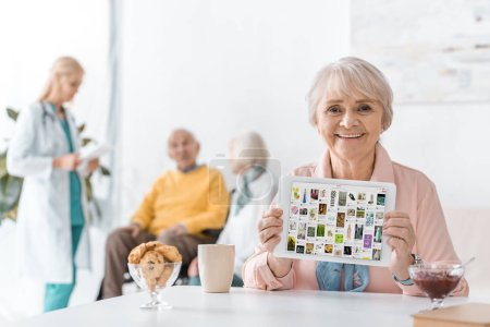 senior woman showing pinterest app on digital tablet screen at nursing home